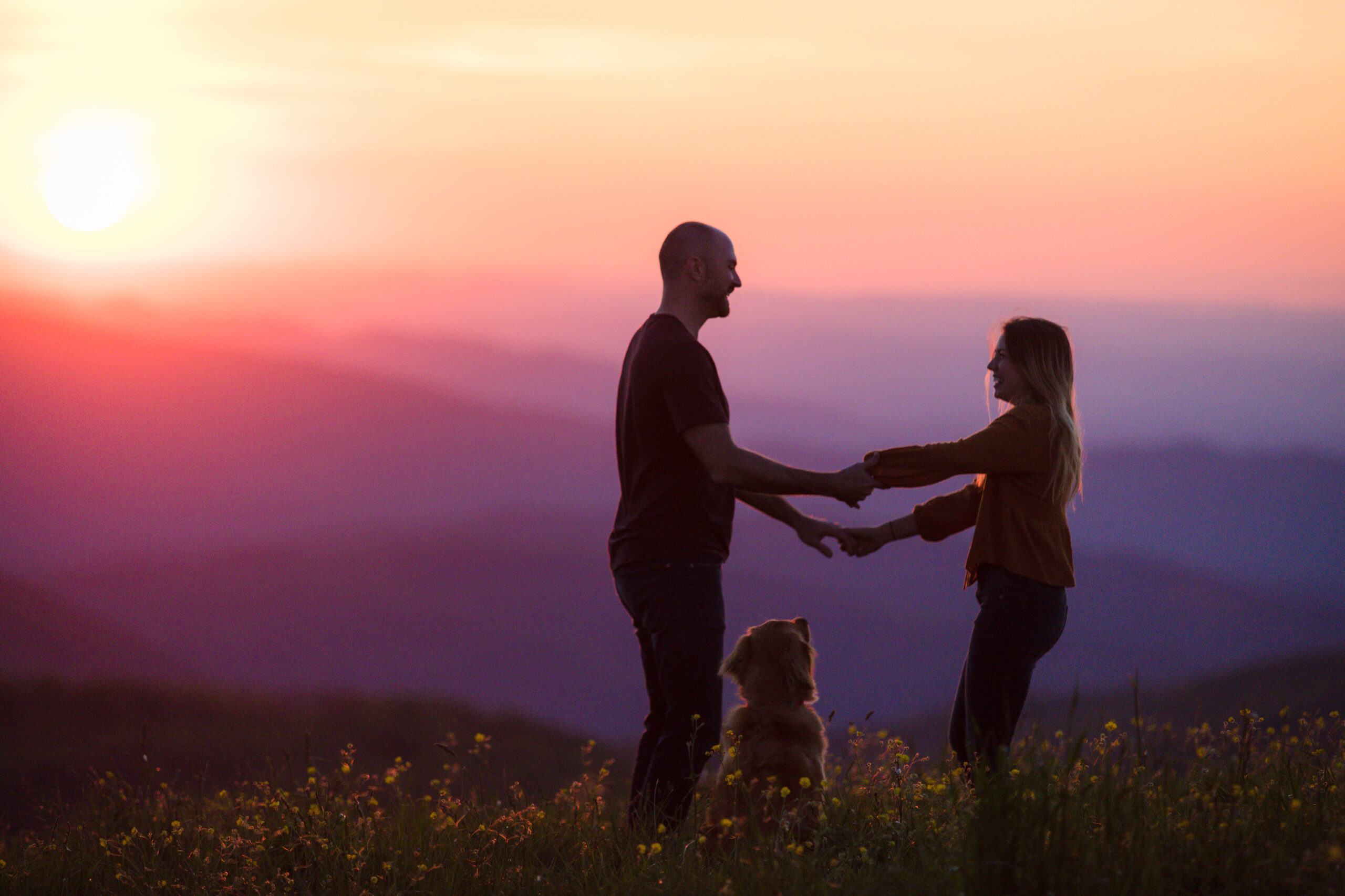 Asheville Proposal Photographer -A picture have a couple dancing in a field of yellow flower with purple and orange mountains in the background