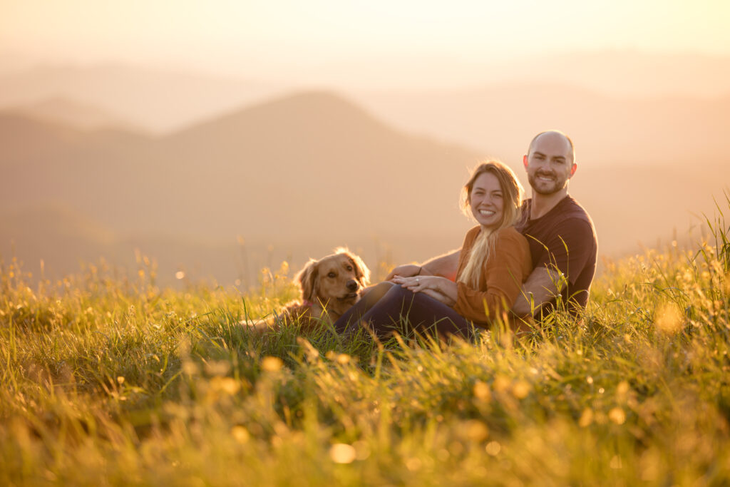 Golden hour photo on Max Patch. Couple with dog sitting in field with mountain tops in background.