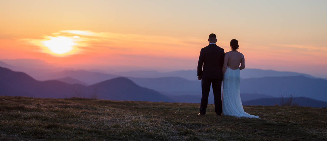 Andrews Bald & Clingmans Dome is one of the best Adventure Photography Locations, capturing stunning image of couple standing on top of the bald mountain at sunset. The mountains are purple and the sun is bright orange.