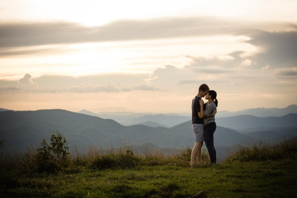 Asheville proposal photography adventure on top of black balsam. Newly engaged couple embracing one another on top of the mountain with distant views of the Blue Ridge Parkway and other peaks