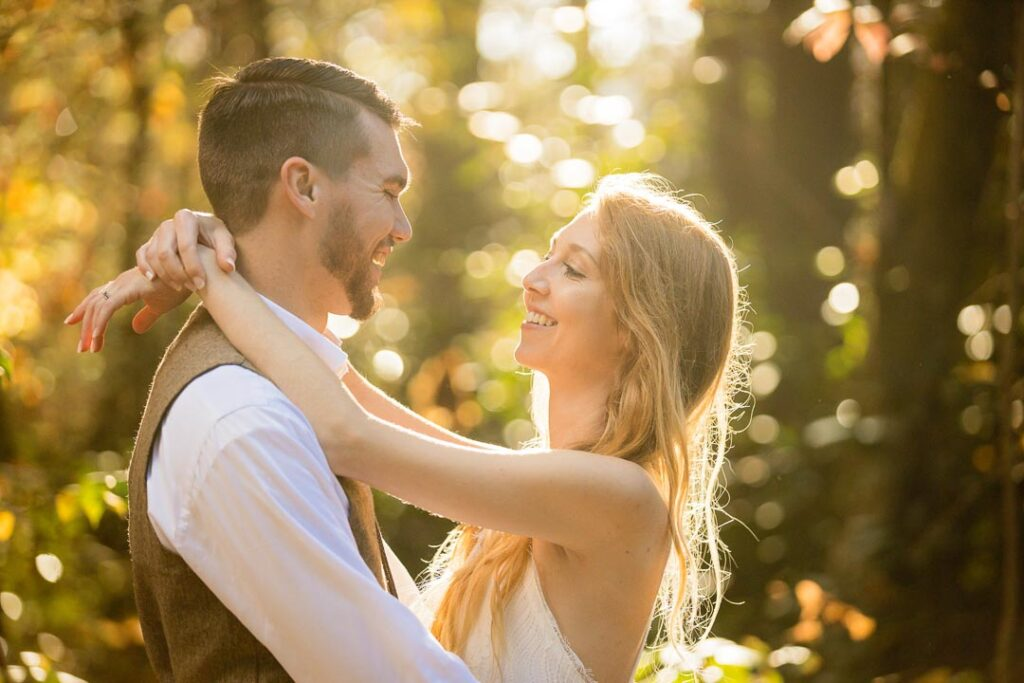 A newly proposed engaged couple in DuPont state forest out for an adventure. The couple holds each other as sunlight breaks through the forest, lighting her blonde hair in a golden bath. Both are visibly happy from the proposal and smiling at one another