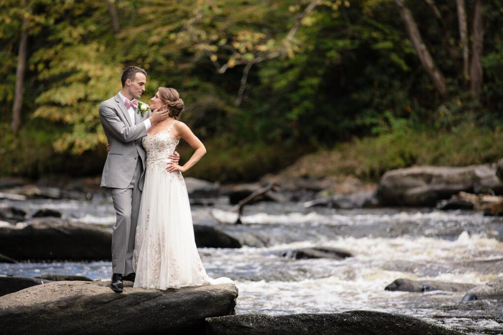 Couple in wedding outfit holding one another posing on a rock in the middle of the River you can see the white water washing by
