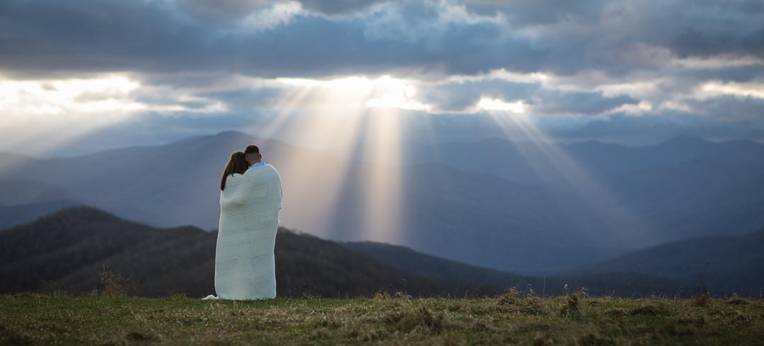 A newly engaged couple stands on top of Max Patch, looking off into the distance as sun rays peek through the clouds onto the distant mountain tops.