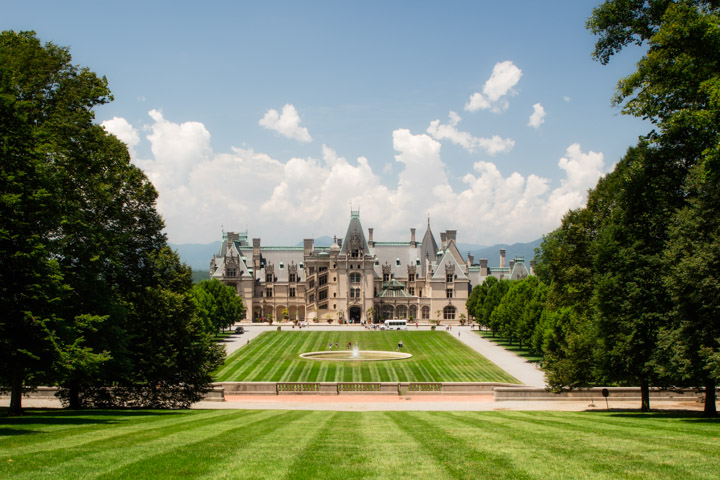 View from Diana on Biltmore Estate, this is a popular engagement photography location. Looking down the hill the grass is very green and have a straking pattern that leads directly to the Biltmore House. White puffy clouds are in the background among the mountains1